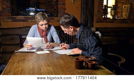 Businessman and businesswoman business partners discussing and signing contract in a restaurant cafe.
