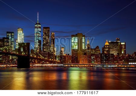 New York City's Brooklyn Bridge and Manhattan skyline illuminated at night