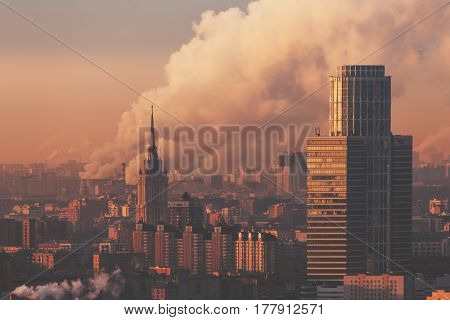 Close-up shooting from top of morning metropolitan city: tower and office business skyscraper residential buildings and districts huge smoke from chimneys in background hazy horizon