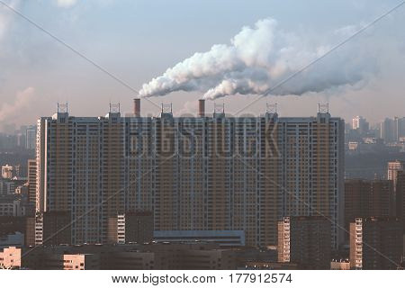 View from top of huge residential ship-like house with multiple regular windows and two big chimneys with smoke behind on sunny morning in residential district of metropolitan city