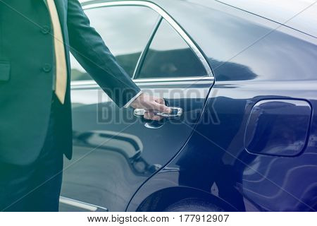 Businessman opening limo car door