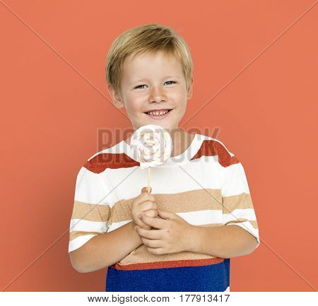 Little boy smiling and holding sweet candy lollipop