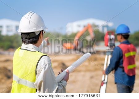 Construction engineer hodling construction drawing with foreman worker checking construction site for new Infrastructure construction project