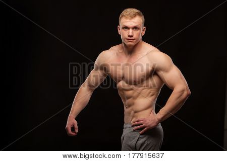 Athletic handsome man fitness-model showing six pack abs and oblique abdominal muscles. isolated on black background with copyspace.