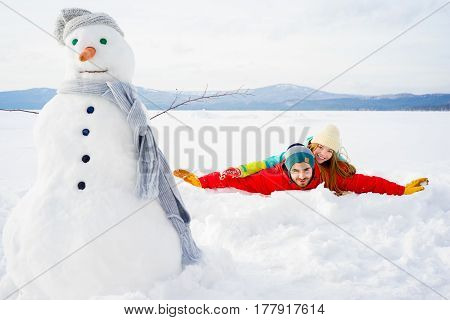 A happy couple is lying in snow on a winter lake after they had a good time playing snowballs and making a snow man