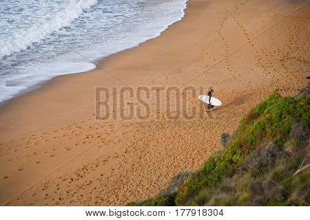 TORQUAY, AUSTRALIA - JULY 20, 2016 : surfer man on the beach with water wave in the sea from top view at Bells beach Torquay Australia.