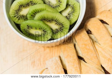 sliced pieces kiwi in white bowl with a puff pastry chocolate bun