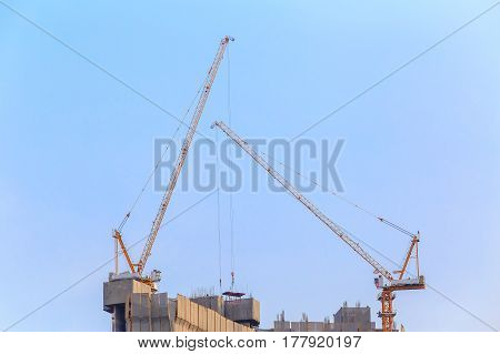 Two Tower Crane and building construction site with contractor on the top. Industrial building.