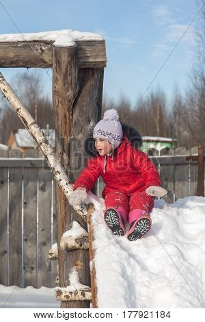 Little cheerful girl on a playground in winter