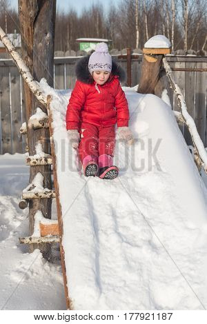 Little girl is riding while sitting on the snow