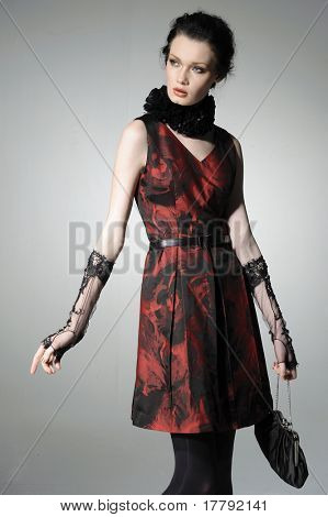fashion model holding handbag posing in light background