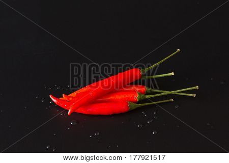 Group of red chili pepers on black background