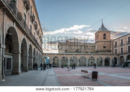Avila Spain - November 11 2014: People in Town Hall square called Mercado Chico a cloudy day at sunset. The old city and its extramural churches were declared a World Heritage site by UNESCO