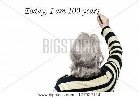Gray-haired old woman writing on a wall: today, I am 100 years, isolated on a white background