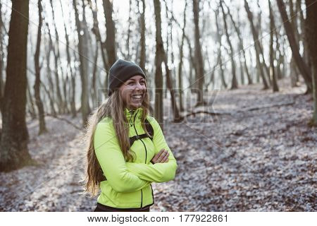 Portrait of beautiful young woman wearing tracksuit, standing in the misty forest. Active woman portrait.