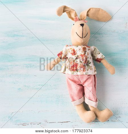 Easter Bunny Doll Over Turquoise Pastel Wooden Backdrop