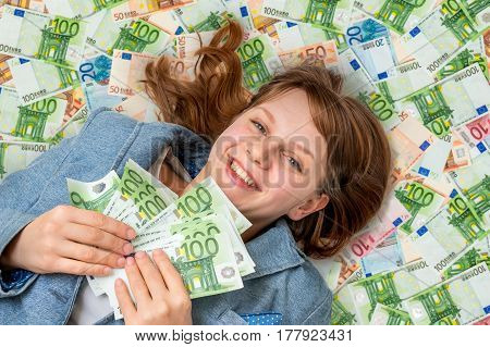 Young Beautiful Woman Lying On Euro Money Background