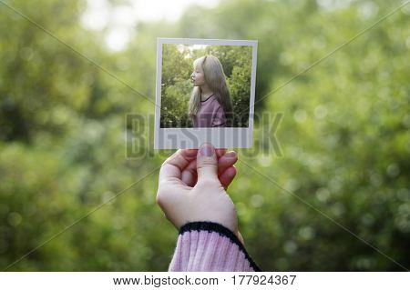 Hand showing self portrait frame with nature