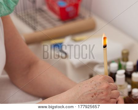 Terapist doing ear candling Alternative therapy session natural medicine health care.
