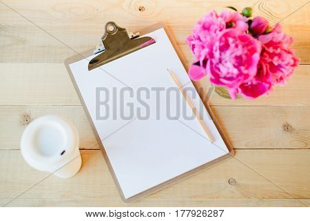 Top view flat lay of blank clipboard with pencil, cup of coffee and pink peony bouquet on wooden background