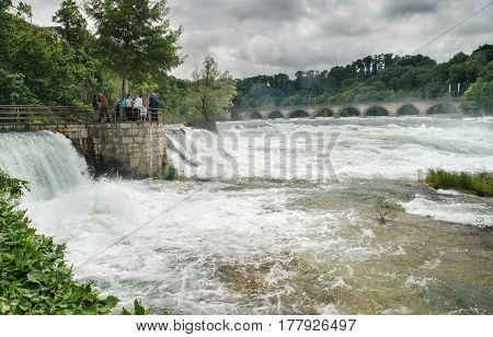 Tourist Looking At Rheinfall, Largest Plain Waterfall In Europe