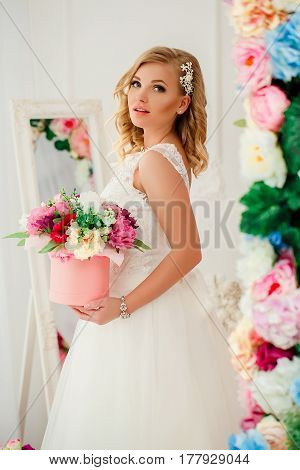 Young blonde pretty woman wearing wedding dress posing near bed decorated with flowers.