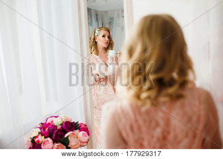 Young blonde pretty woman in romantic negligee near bed decorated with flowers.