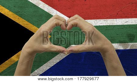 With a stylized South African flag background an anonymous person's hands being held in the form of a heart, symbolizing love and patriotism for South Africa.