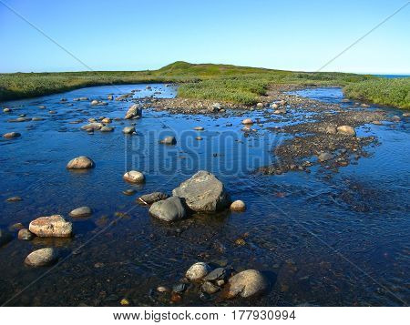 Background blurred view landscape shallow river flowing over the plateau and flowing into the Barents Sea on the Rybachiy peninsula, Murmansk region