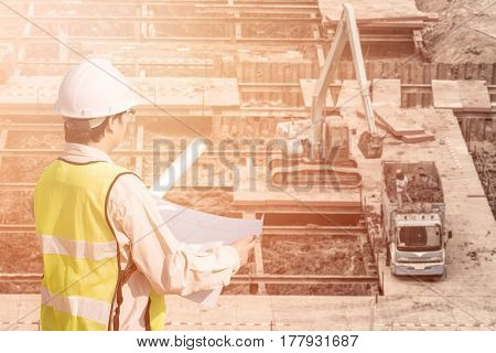 Construction engineer checking construction drawing with construction site in background for new Infrastructure construction project concept