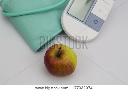 A healthy scene for World Health Day consisting of a blood pressure monitor and a nice fresh apple