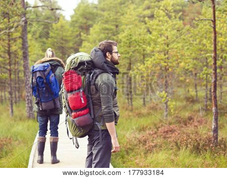 Two bearded men walking in swamps in autumn forest. Camp, adventure, traveling and fishing concept.