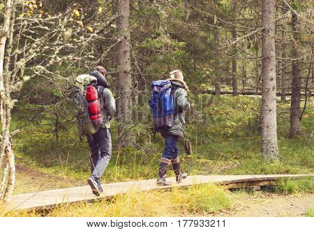 Two handsome, bearded men with backpacks hiking in swamps. Camp, adventure, traveling and trip concept.