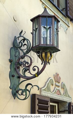 Stylized antique lamp on the wall of the house. Austria Tyrol Mayrhofen.