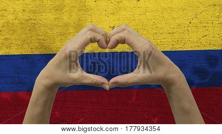With a stylized Colombian flag background an anonymous person's hands being held in the form of a heart, symbolizing love and patriotism for Colombia.