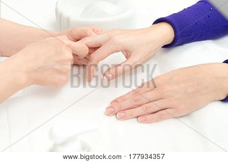 French Manicure process in beauty salon close up of female hands