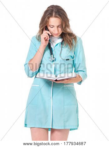 Beautiful young doctor with notepad and talking on cell phone isolated on white background