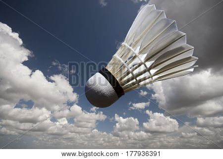 Shuttlecock high up in the sky with clouds.