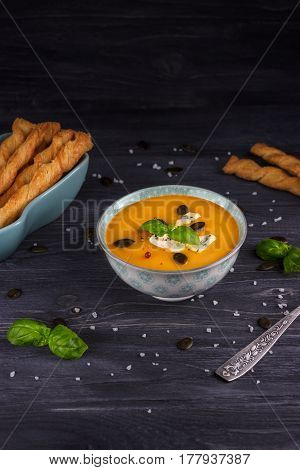 Pumpkin and carrot cream soup on a dark wooden background