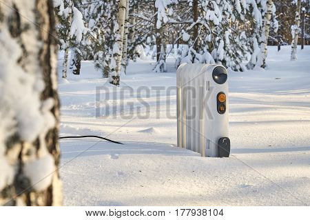 Heating radiator standing in snowy winter forest