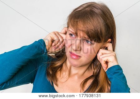 Woman Closes Ears With Fingers To Protect From Loud Noise