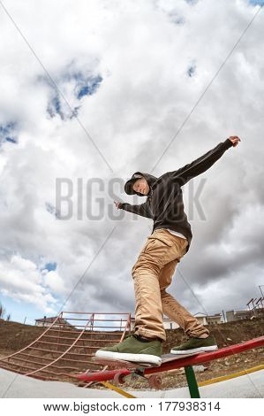 Teen skater in a hoodie sweatshirt and jeans slides over a railing on a skateboard in a skate park, Wide angle