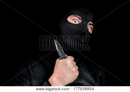 Masked Man In Balaclava With Knife Isolated On Black