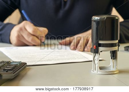 Businessman sitting at office desk and signing a contract