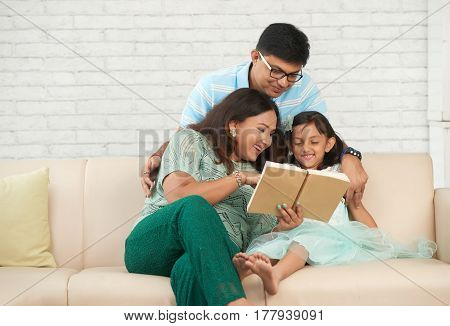 Happy Indian family sitting on sofa and reading a book