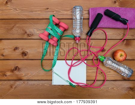 Fitness concept with towel apples stopwatch bottle of water measure tape notebook and skipping rope on wooden table background