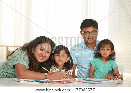 Indian mother, father and two their daughters drawing together