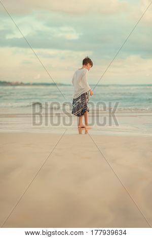 On a hot day, a little boy on the beach is on the beach