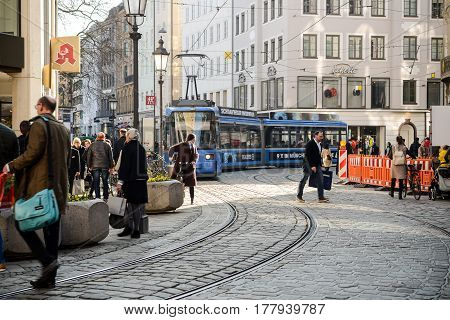 Munich,Germany-March 23,2017:A streetcar approaches as people cross the tracks in a sunny spring afternoon