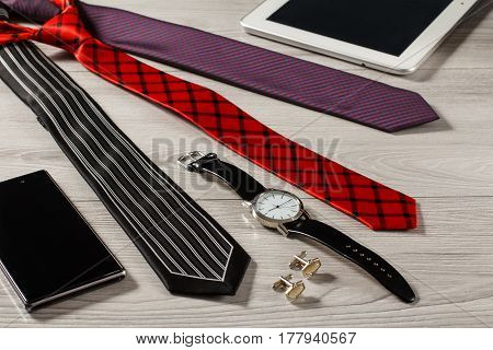 Color silk neckties watch with a leather strap cufflinks sell phonetablet on a gray wooden background